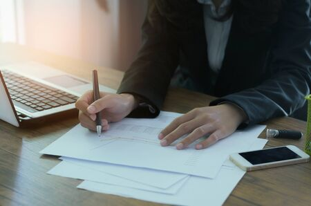 attractive business woman working on table in office with laptop and holding pen point on graph on paper document to analysis about business and marketing growing.
