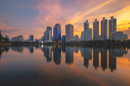 cityscapes building in modern skyline city at morning twilight golden hour with sunrise and water reflection.