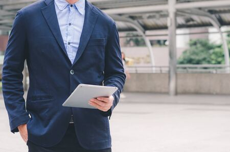 attractive business man using touching pad on smartphone tablet technology connecting social online.
