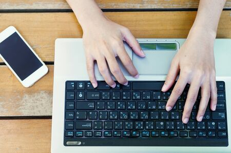 attractive hand of business woman using laptop working typing key board at outdoor on wooden table with mobile phone.