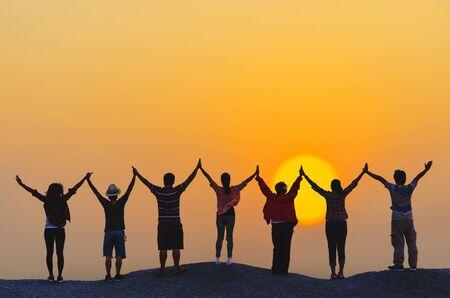 concepto de trabajo en equipo silueta diversidad la gente muestra las manos en lo alto sobre la cabeza socio exitoso juntos al atardecer en la cima de la colina de la roca.
