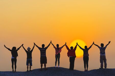 teamwork concept silhouette diversity people show hands high up over head successful partner together at sunset on top rock hill.