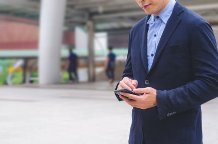 attractive business man using touching pad on smartphone technology connecting social online. Banco de Imagens