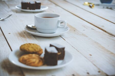 chocolate cookies and brownie in white plate on wood table with coffee cup at morning with sunrise. dessert and coffee concept.