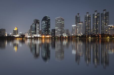 cityscapes building in modern city bright at night with skyline and water reflection.