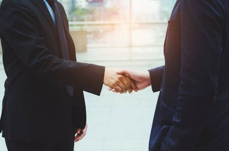 attractive business man shaking hand for complete deal together business successful at outdoor in city. teamwork concept. partnership concept and dealership concept.