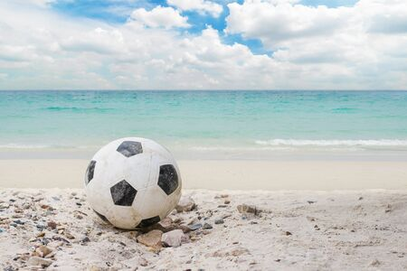 football or soccer put on the beach with blue aqua sea water and white cloud blue sky on vacation day at summer.