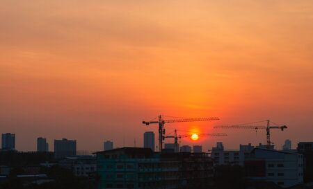 silhouette view of urban infrastructure people property construction project with high cranes liftting in big city in morning skyline with sunrise golden hour. Banco de Imagens