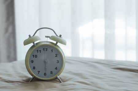 alarm clock on the bed in bedroom at holiday on morning. wake up time concept.