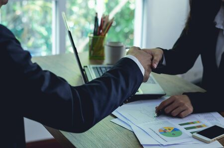 business man and business woman shaking hand complete deal together business successful in office with stationery on table. teamwork concept. partnership concept and dealership concept.