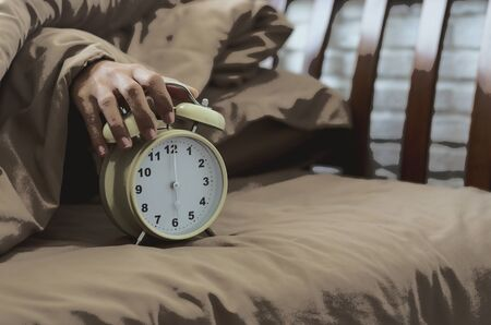 alarm clock with lazy woman hand put on for stop alarm clock to snooze from wake up on bed in bedroom at holiday morning with oil paint effect style.