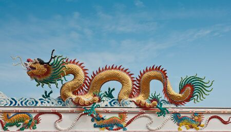 Dragon statute on the roof with blue sky background