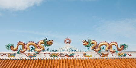 Couple of dragon statutes on the roof with blue sky background