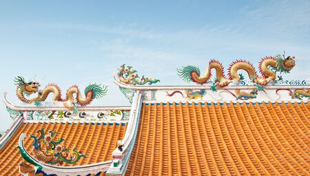 Couple of dragon statuses on the roof with blue sky background