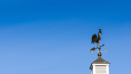 Weather vane against blue sky photo