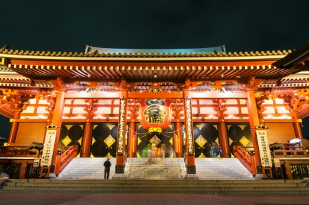 Famous Tokyo landmark, Asakusa Temple colorful entrance by night with silhouettes of prayers Tokyo, Japan