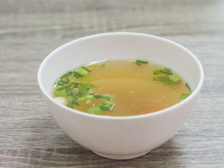 scallion: thai chicken soup  with scallion , white bowl, gray wood background