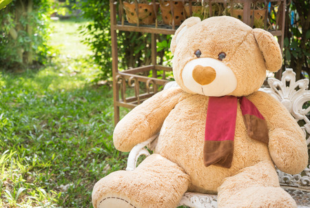 furry stuff: big bear doll sit on the chair, blur garden and sunshine background