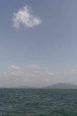 gently: blue sky , gently white cloud and ocean , vertical pale picture