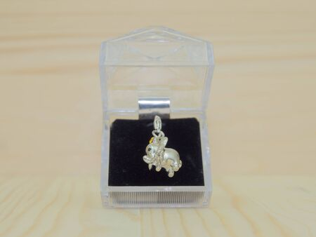 locket: lovely crystal locket in box, blur wooden background