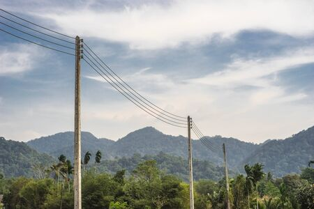 gently: electricity post beside mountain view with few mist and gently cloud