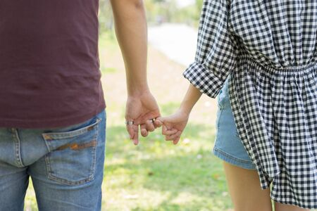 little finger: man and woman hook each others little finger