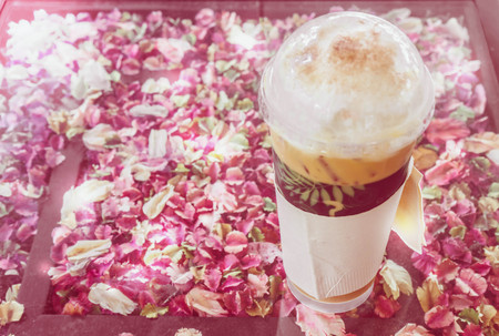 contain: plastic cup of ice cappuccino on glass table that contain a lot of dry petal,blur sweet picture