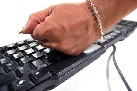 The hand is smashing the black keyboard in anger.