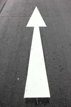 The white arrow direction painted on road photo