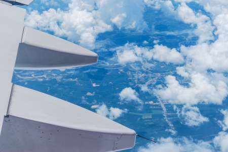 View of jet plane wing and blue sky photo