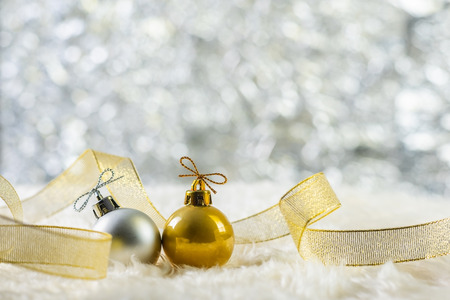 gold and silver Christmas ball on wool, twinkle bokeh background