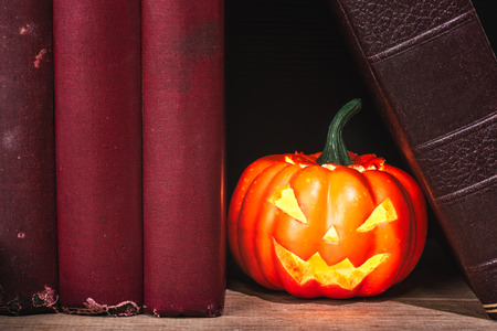 Close-up of halloween pumpkin between old books on wooden table