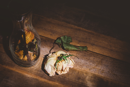 Withered dry rose and leaves falling from vase on wooden table Archivio Fotografico