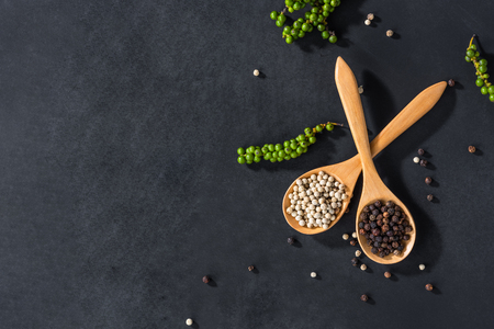 Ground white and black pepper in wooden spoon on black table decorated with pepper corn, top view Imagens