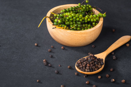 Close-up of ground black pepper in wooden spoon on black table