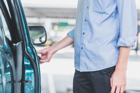 Gros plan de la main de l'homme ouvrant la porte de la voiture