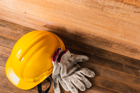 engineer or foreman safety helmet and gloves on wooden table