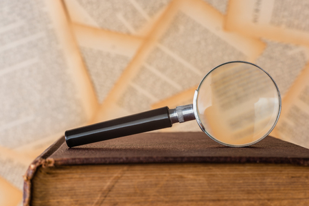 close-up magnifying glass place on old book, book pages background Archivio Fotografico