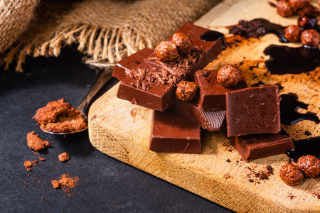 Close-up of dark chocolate bars and other products on wooden cutting board Stok Fotoğraf - 122792821