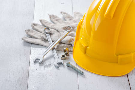 yellow safety helmet and tools on white wooden table