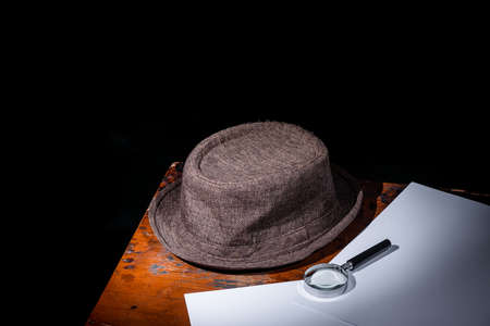 brown hat on decoyed desk and magnifying glass on white blank paper, black background