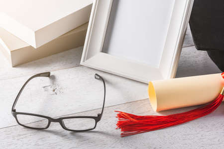 Close-up of glasses and education or graduation equipment background on wooden white table, congratulation concept