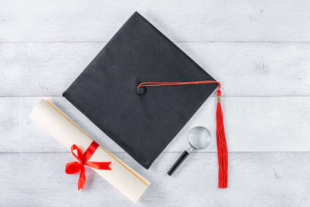 mortarboard, magnifying glass and diploma tied with red ribbon on white wooden table, top view Reklamní fotografie