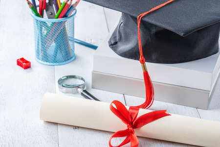 diploma tied with red ribbon on white wooden table Reklamní fotografie