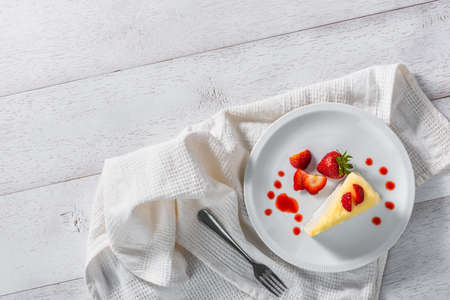 piece of strawberry cake dessert and sauce topping on white dish, top view