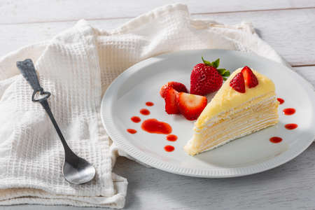 piece of strawberry cake dessert and sauce topping on white dish
