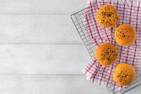 bread buns on stainless sieve on white wooden table background, top view