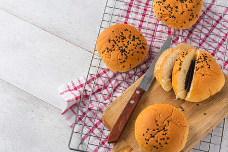 cream red bean bread bun on white wooden table background, top view