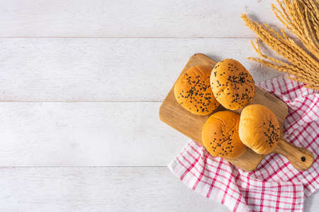 pile of bread buns on wooden cutting board on white wooden table background, top view Reklamní fotografie