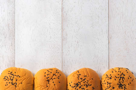 delicious bread bun with black sesame seeds on wooden background, top view